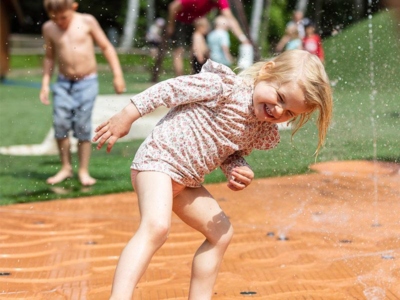 Barn leker i vattenlekplats